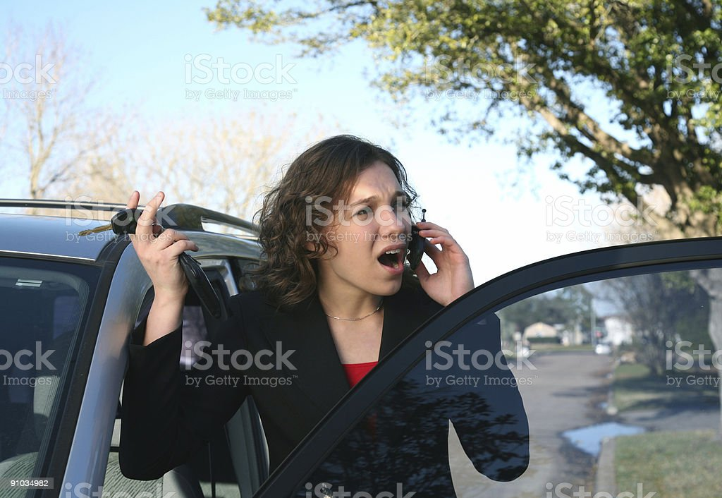 Busy young woman getting into her car stock photo
