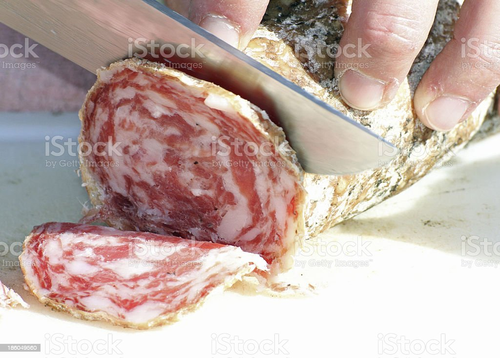 butcher cut the salami with a sharp knife 2 stock photo