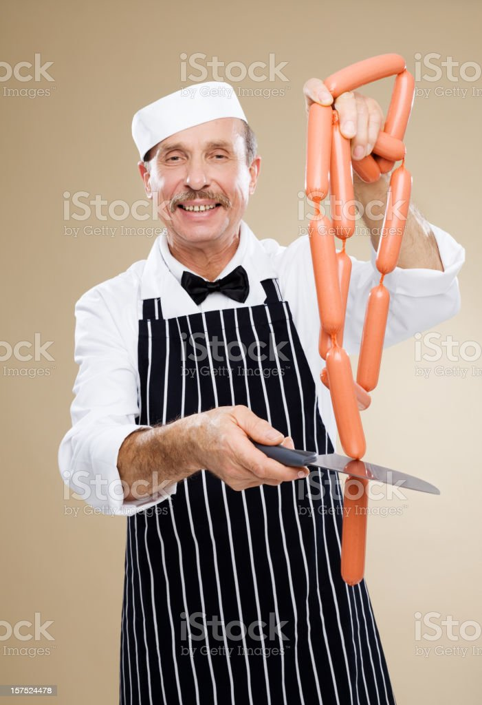 Butcher Cutting A String Of Sausage Links stock photo