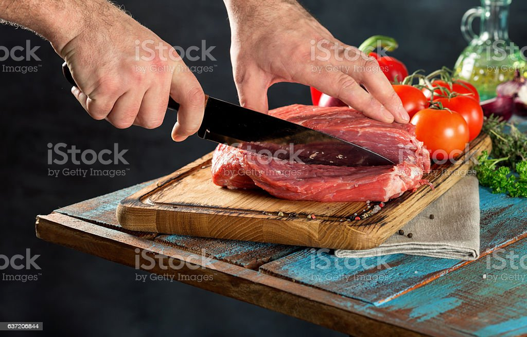 Butcher cutting beef meat on a wooden table stock photo