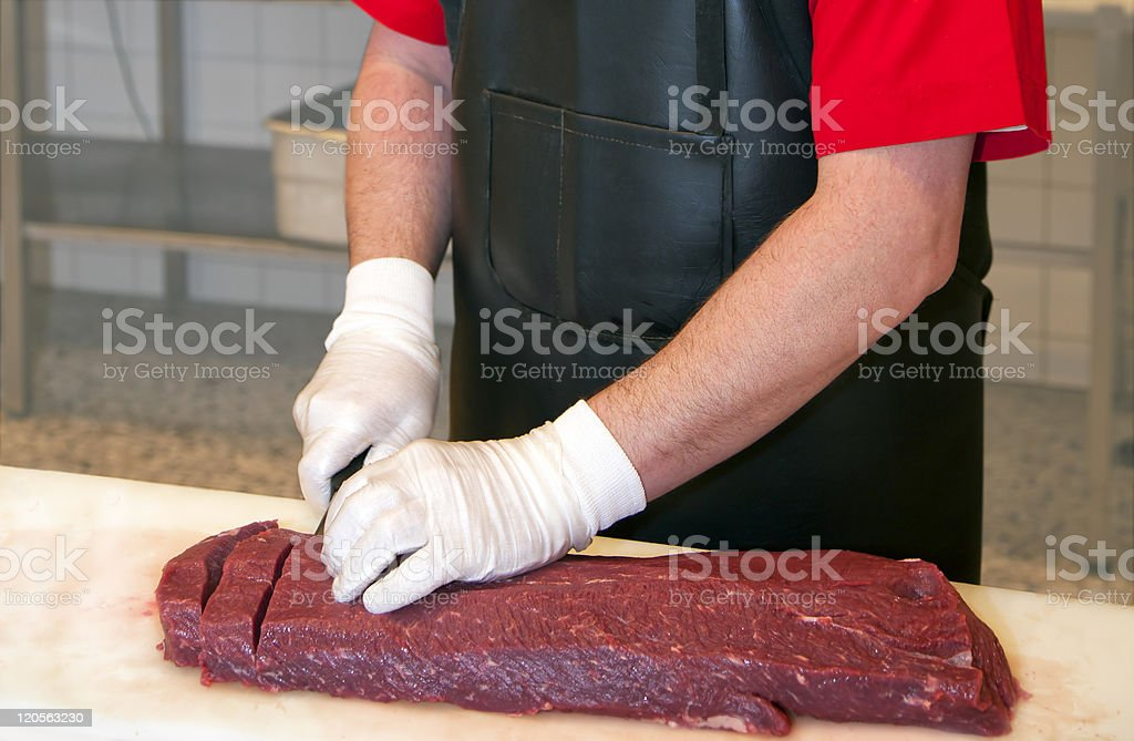 Butcher cutting meat royalty-free stock photo
