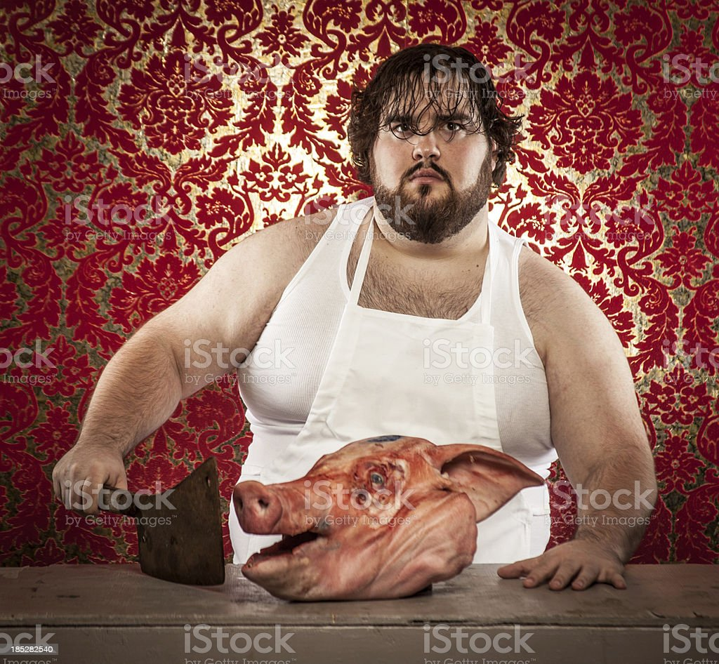 Butcher Cutting Pig's Head with Rusty Cleaver, Hand on Table royalty-free stock photo