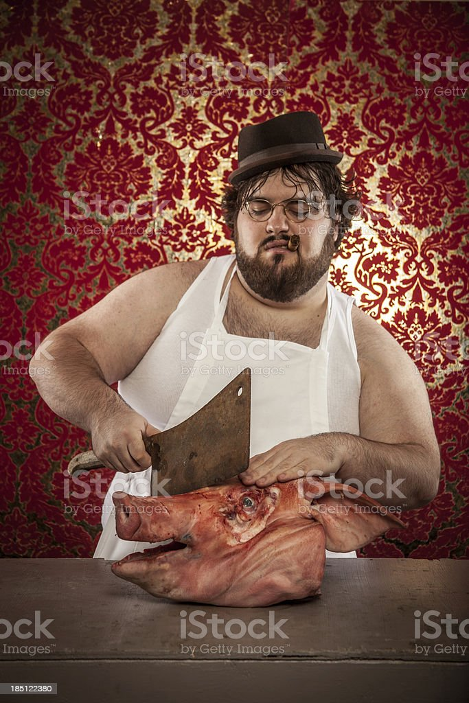 Butcher Cutting Pig's Head with Rusty Cleaver, Looking Down royalty-free stock photo