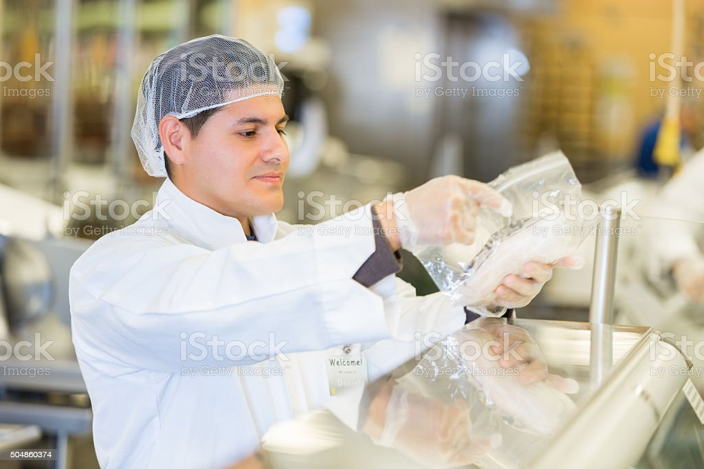 Butcher or deli manager packaging meat for customer in supermarket stock photo