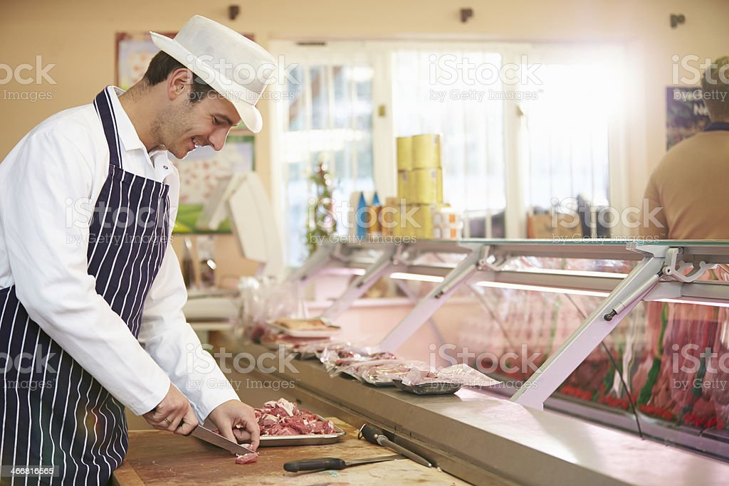 Butcher preparing meat in old fashioned meat market royalty-free stock photo