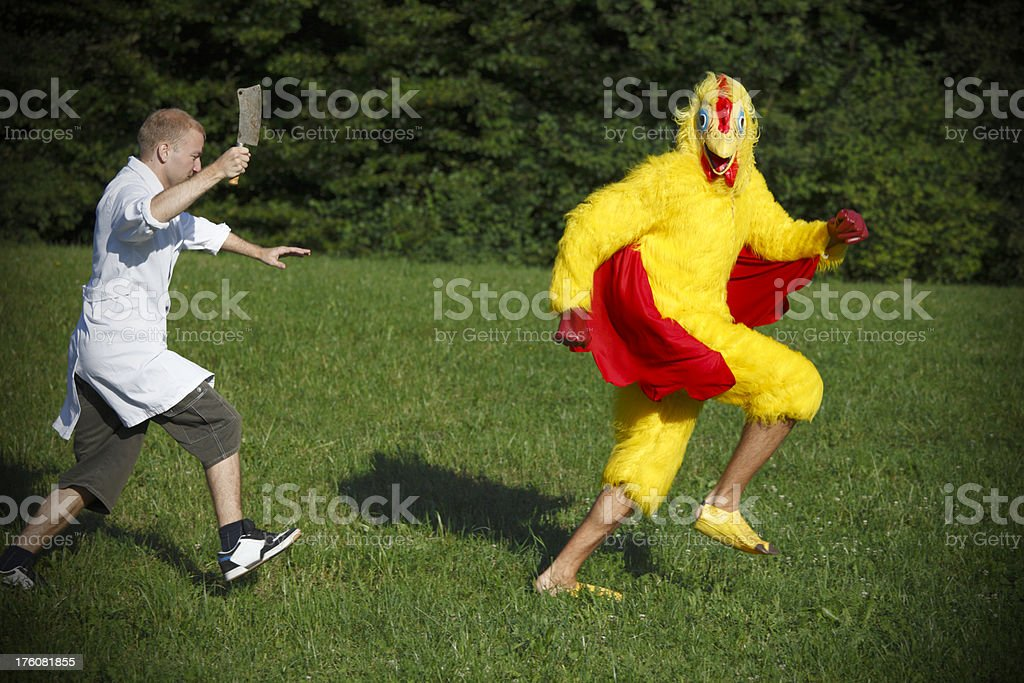 Butcher running after chicken stock photo