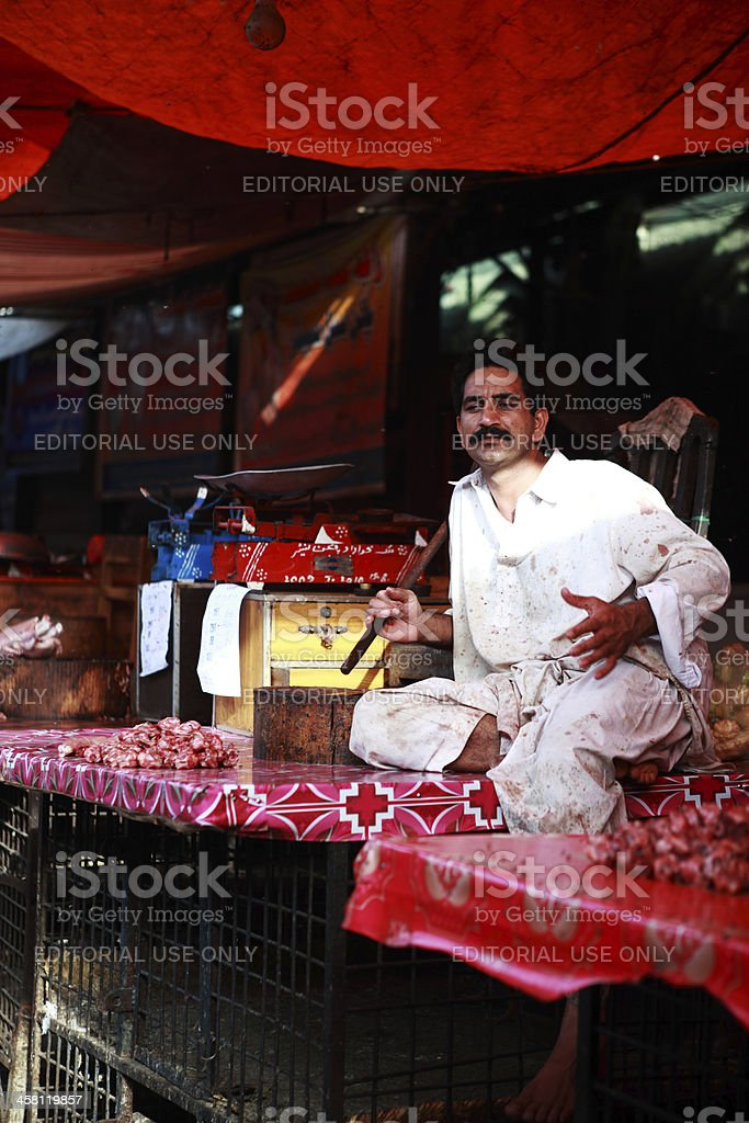 Butcher Sitting over Chicken Cages in Meat Stall stock photo