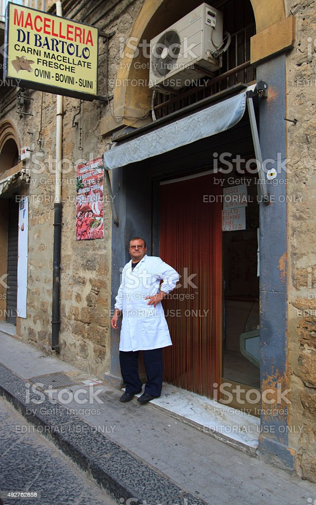Butcher Stands Outside Shop in Piazza Armerina, Sicily stock photo