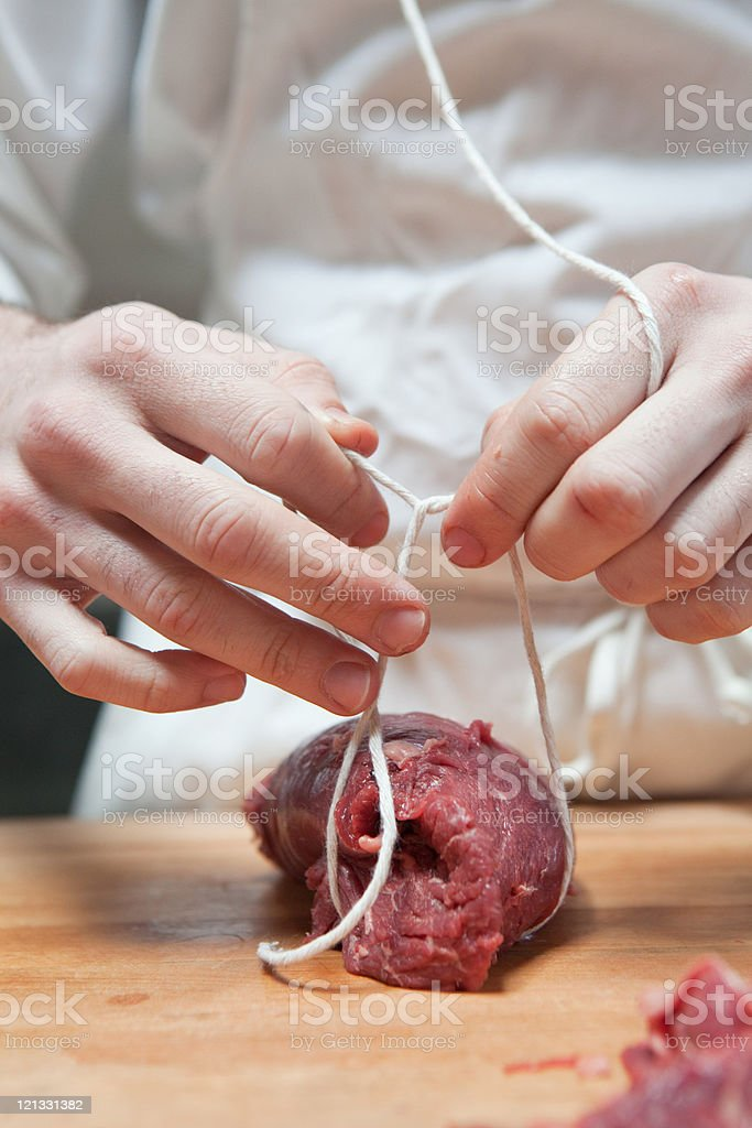 Butcher tying beef tenderloin with string stock photo