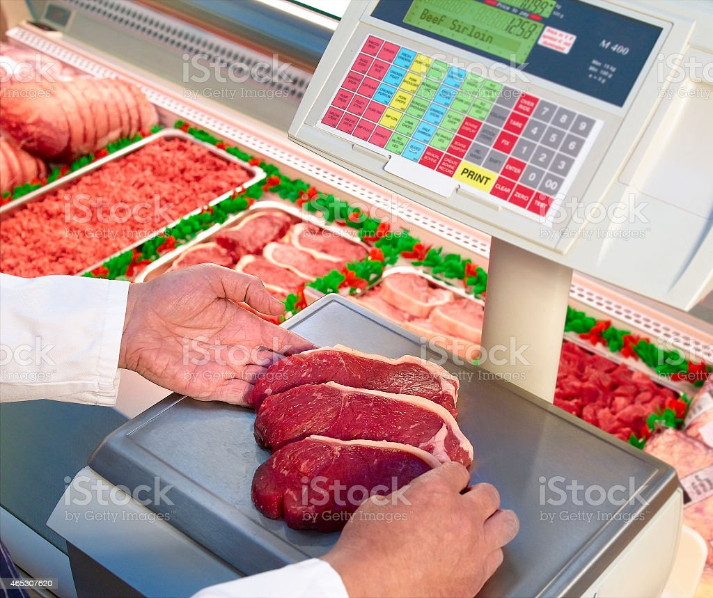 Butcher weighing beef meat steaks on scales stock photo
