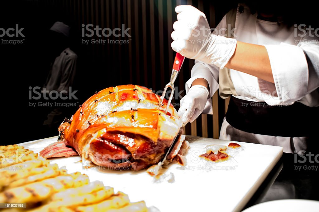 butcher's hand while fast cuts a piece of raw ham, stock photo