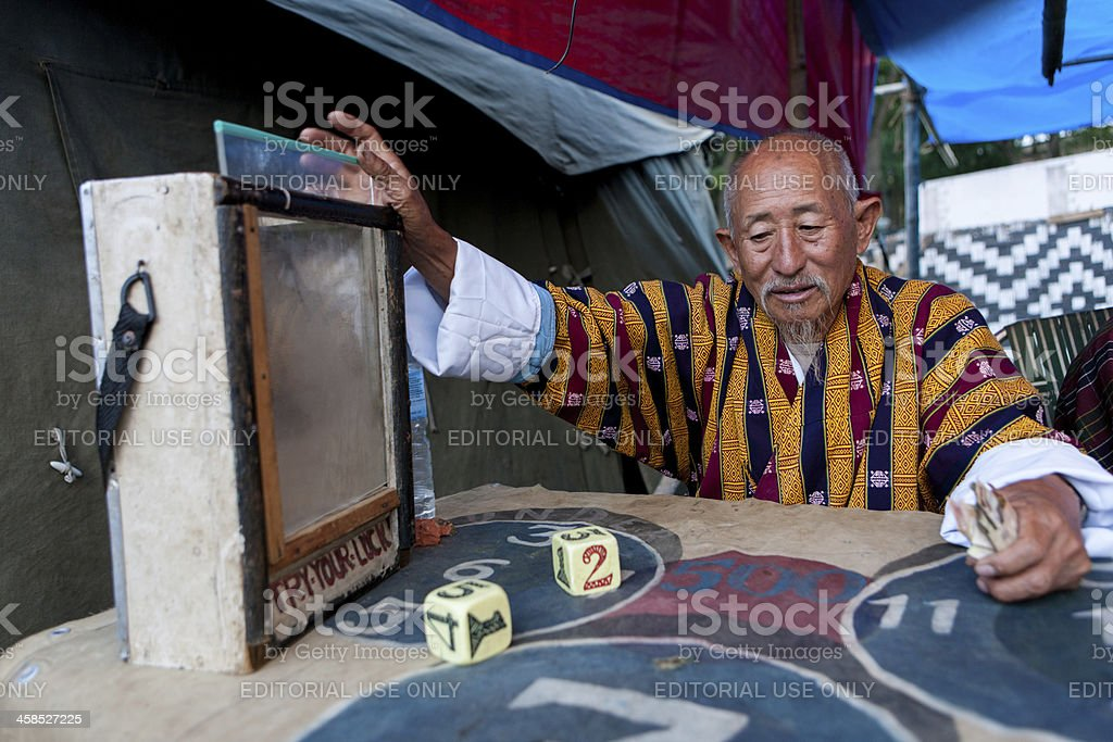 Buthanese man invites people for game of dice royalty-free stock photo