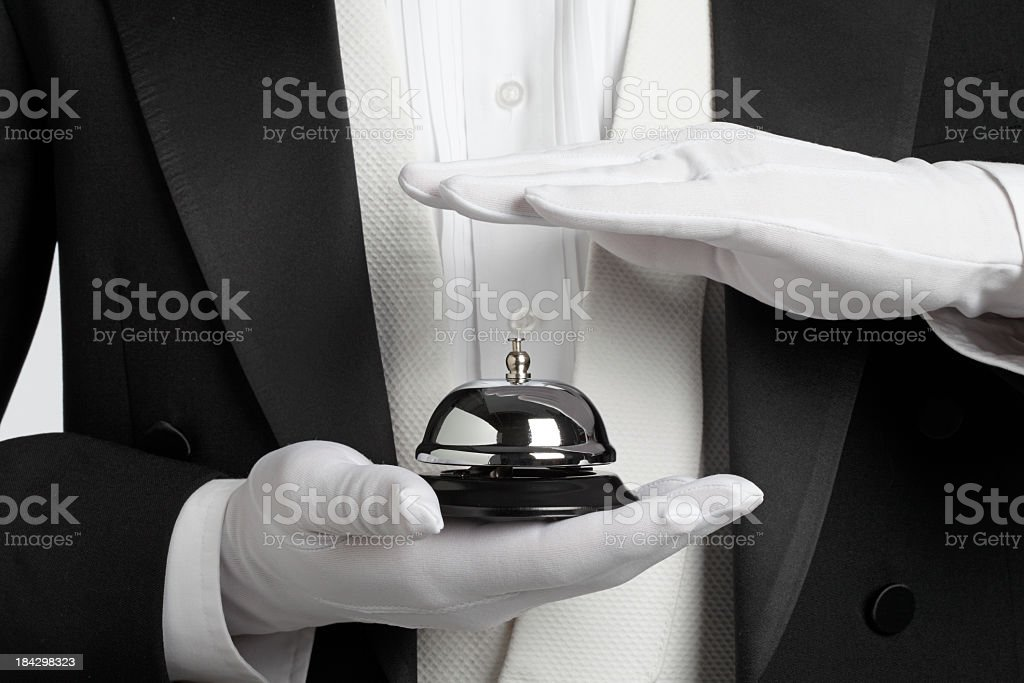 Butler holding and about to ring a service bell stock photo