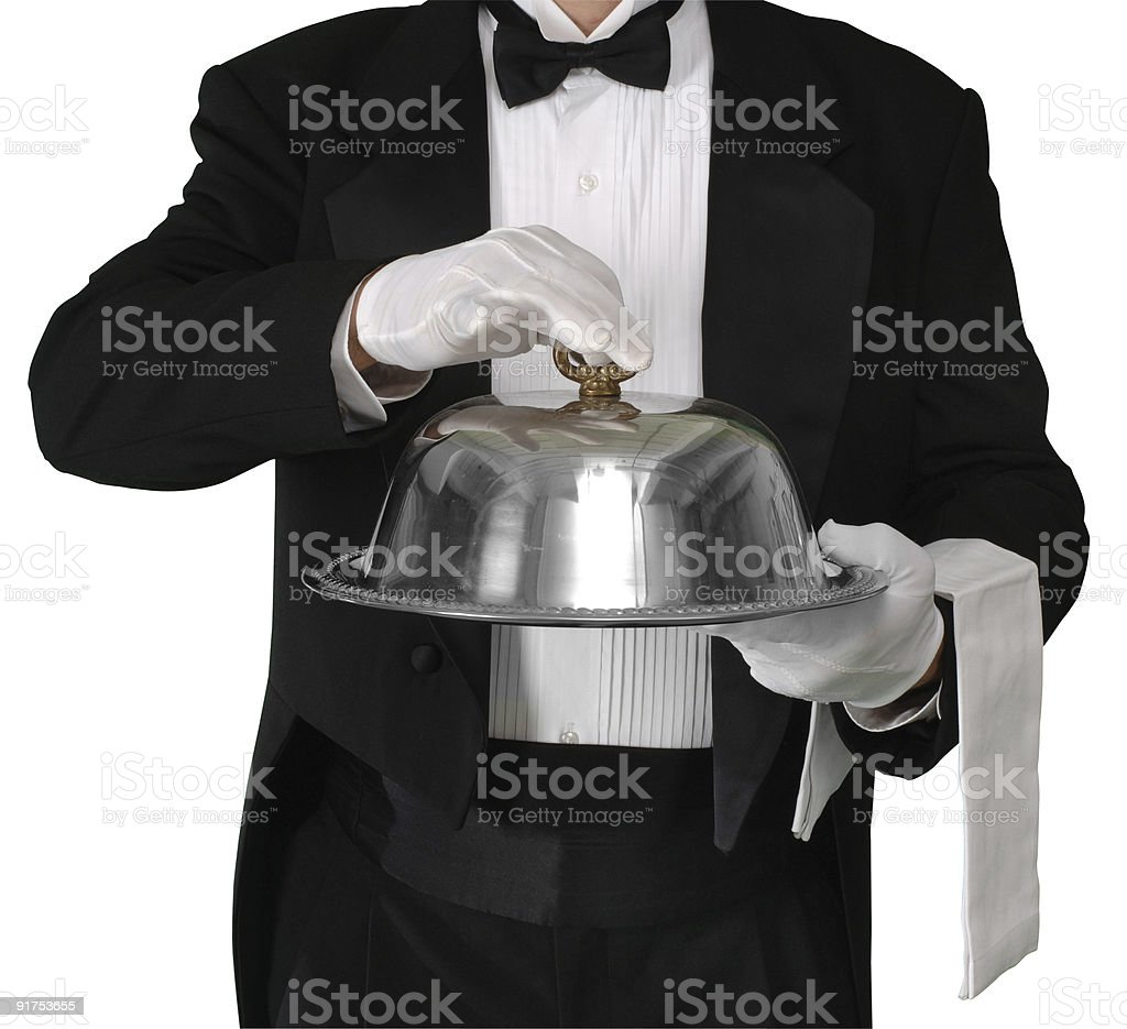 Butler holds dish of food ready to serve stock photo