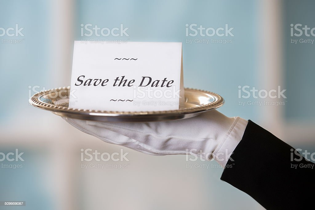 Butler holds 'Save the Date' notecard on silver platter. Window. stock photo