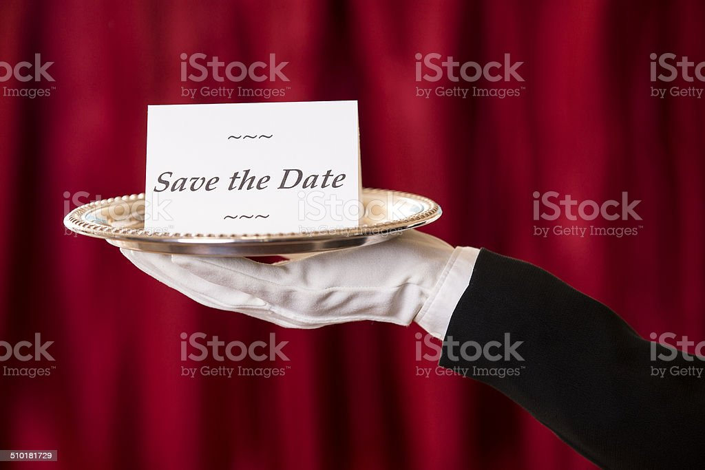 Butler holds 'Save the Date' notecard, silver platter. Red curtains. stock photo