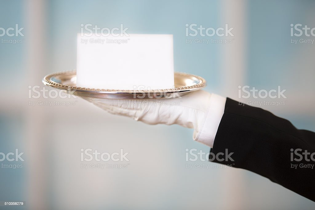 Butler holds white, blank notecard on silver platter. Window background. stock photo