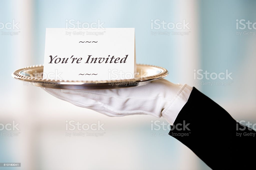 Butler holds 'You're Invited' notecard on silver platter. stock photo