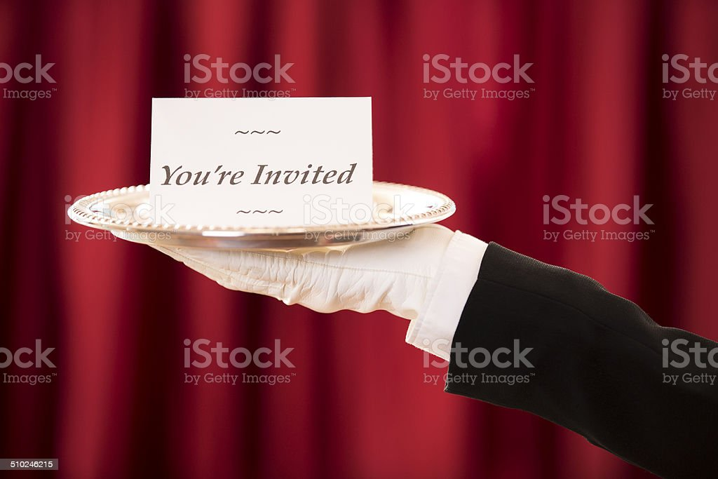 Butler holds 'You're Invited' notecard on silver platter. Red curtains. stock photo