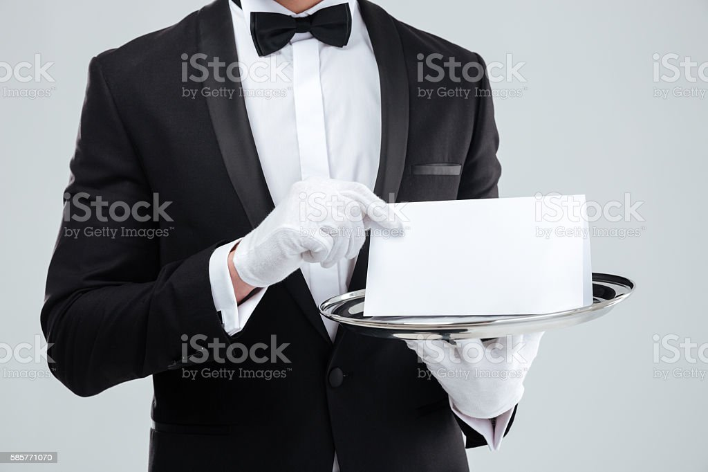 Butler in tuxedo and gloves holding blank card on tray stock photo