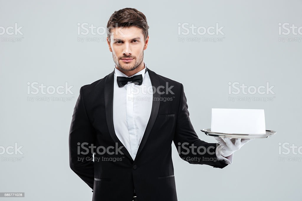Butler in tuxedo and gloves holding tray with blank card stock photo