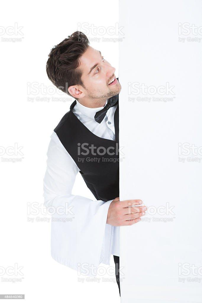 Butler Looking At Blank Billboard stock photo