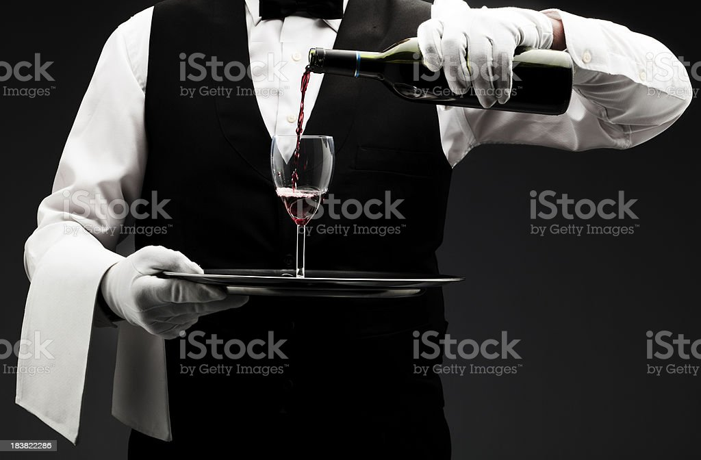 butler pouring wine stock photo