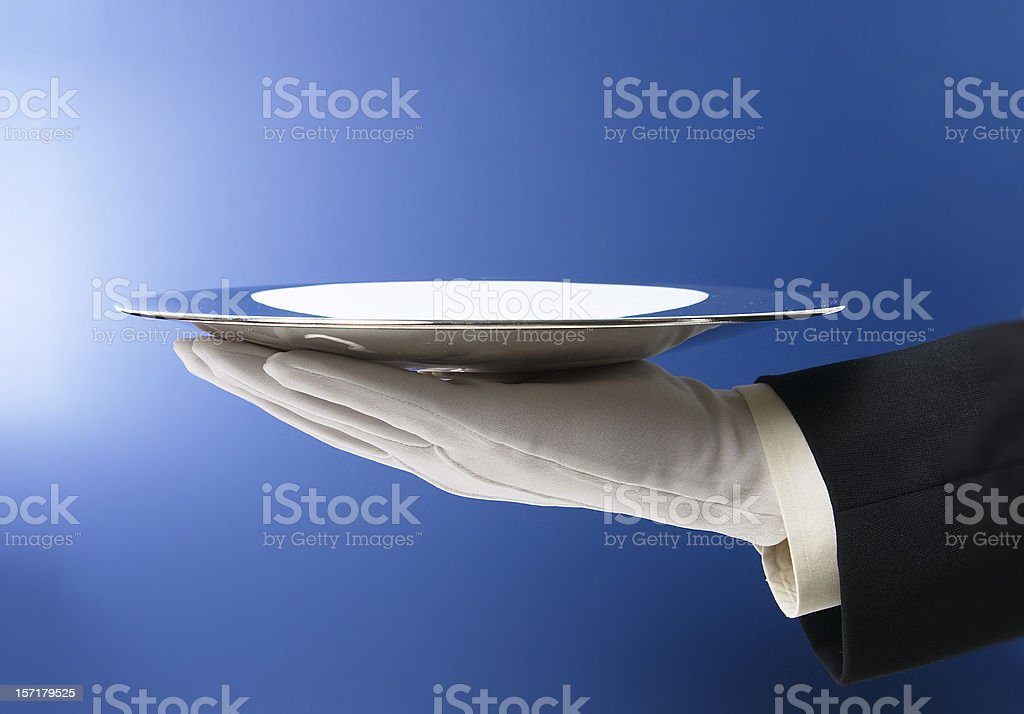 Butler Serving Empty Silver Tray on Blue stock photo