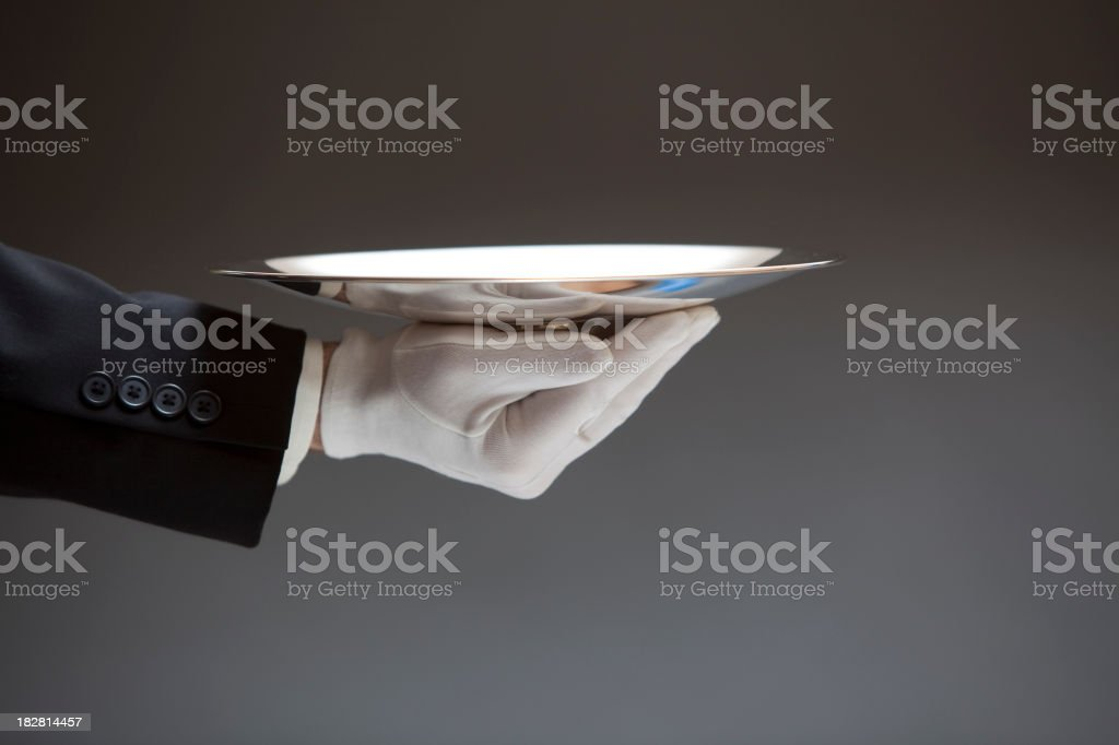 Butler Serving Empty Silver Tray on Gray XXL stock photo