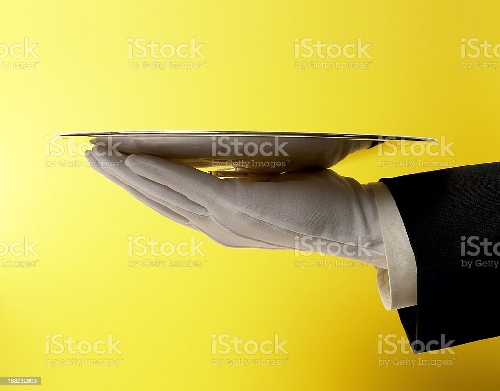 Butler Serving Empty Silver Tray on Yellow stock photo