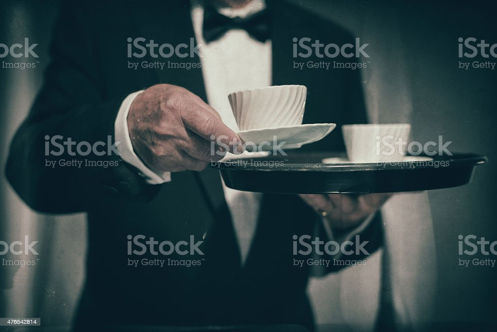 Butler Serving Mug from Tray of White Cups stock photo