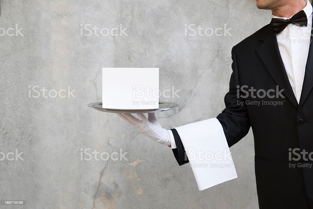 Butler with napkin and silver tray carrying an announcement royalty-free stock photo
