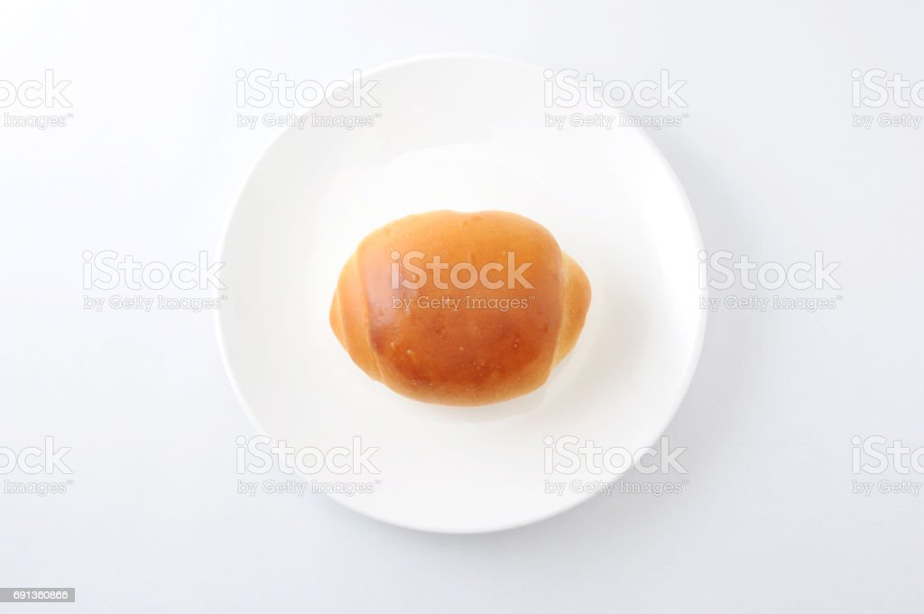 butter bread roll on a plate on white background stock photo