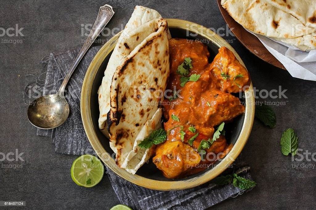Butter Chicken served with homemade Indian Naan bread stock photo