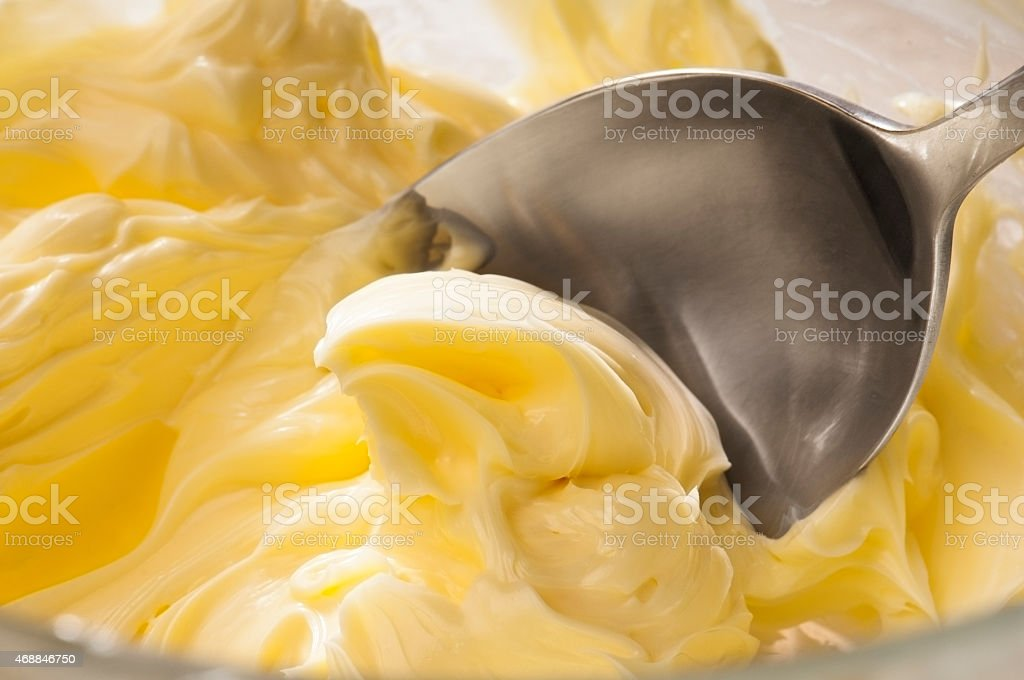Butter cream icing being mixed together with a spoon stock photo