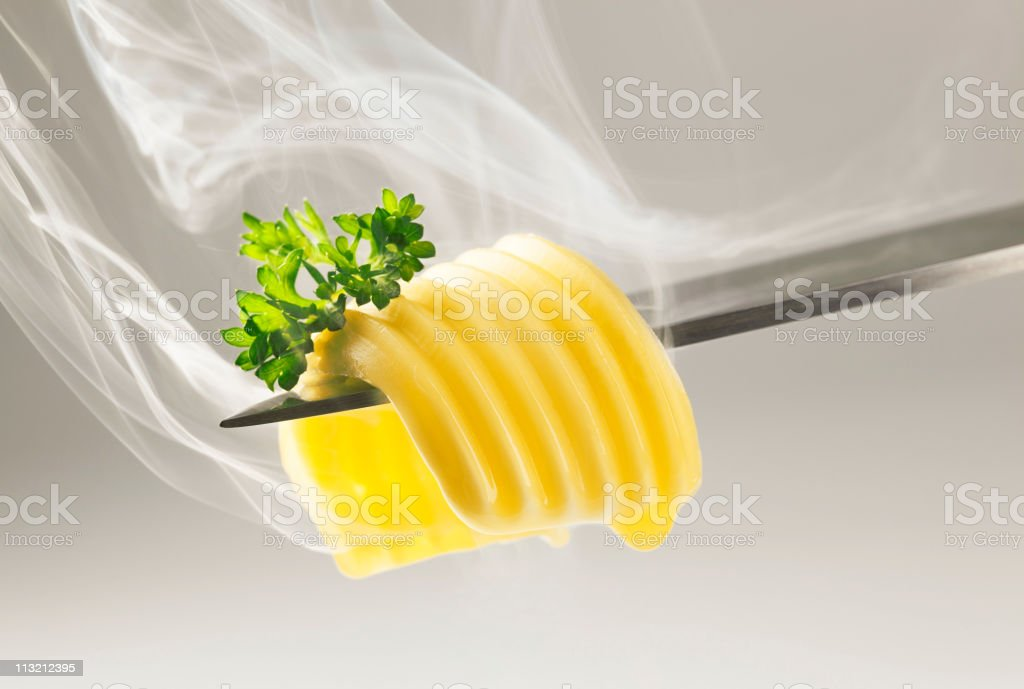 Butter curl melting on a knife stock photo