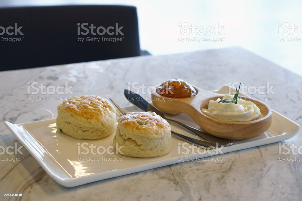 Butter scones served with fresh cream and orange jam on white ceramic tray. stock photo