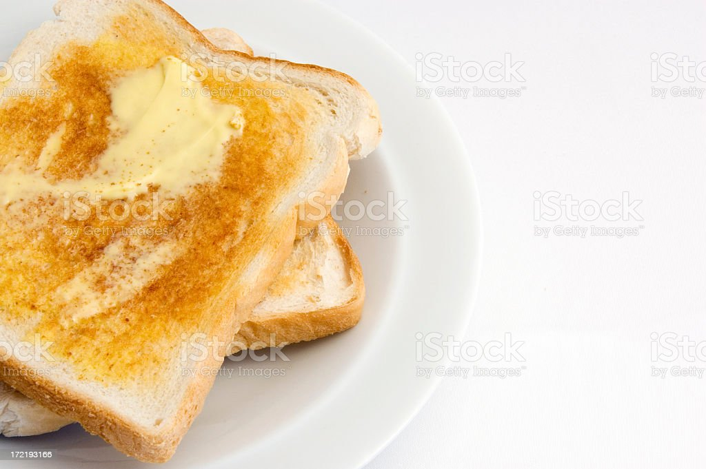 Buttered toast on a white plate against a white background stock photo
