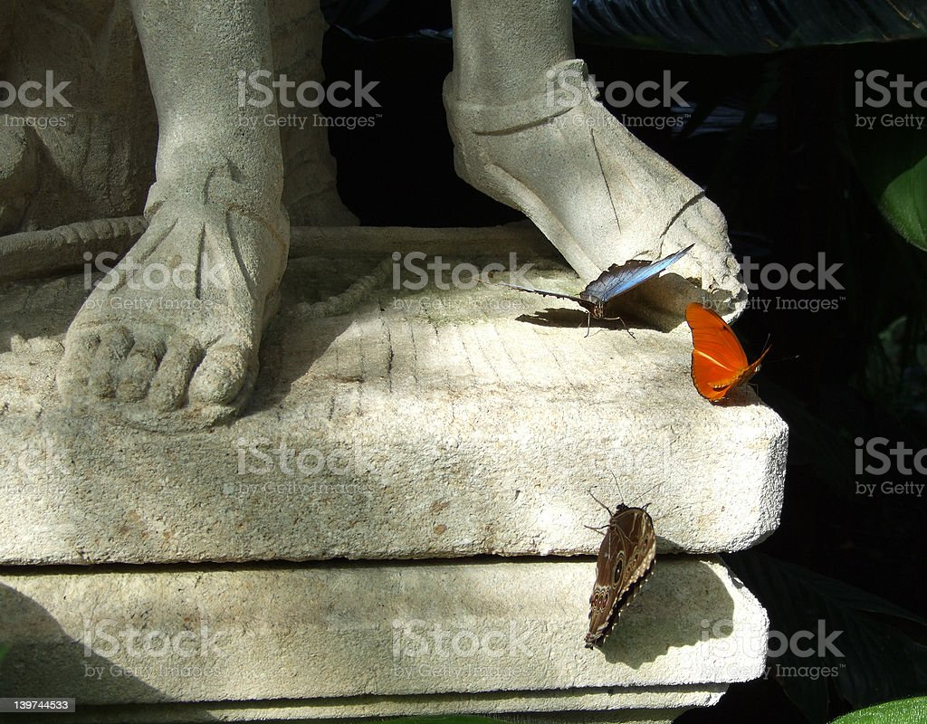 Butterflies at the feet of a sculpture royalty-free stock photo