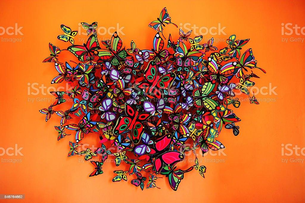 Butterflies heart shape grouping on orange background stock photo