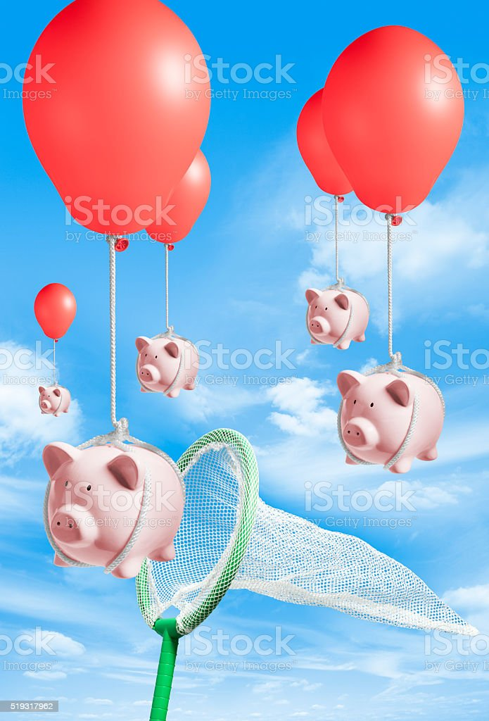 Butterfly fishing net catching piggy banks tied to red balloons stock photo