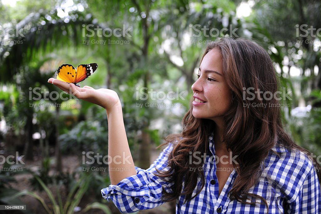 butterfly sitting on hand of a young woman stock photo