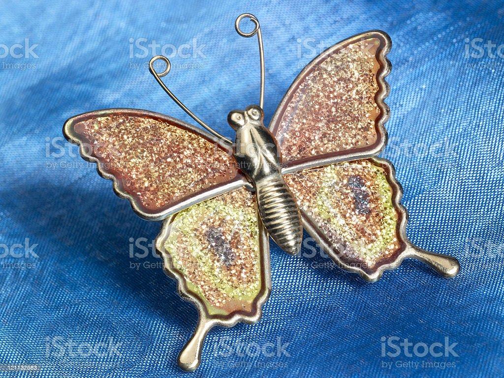 butterfly trinket on blue fabrics royalty-free stock photo