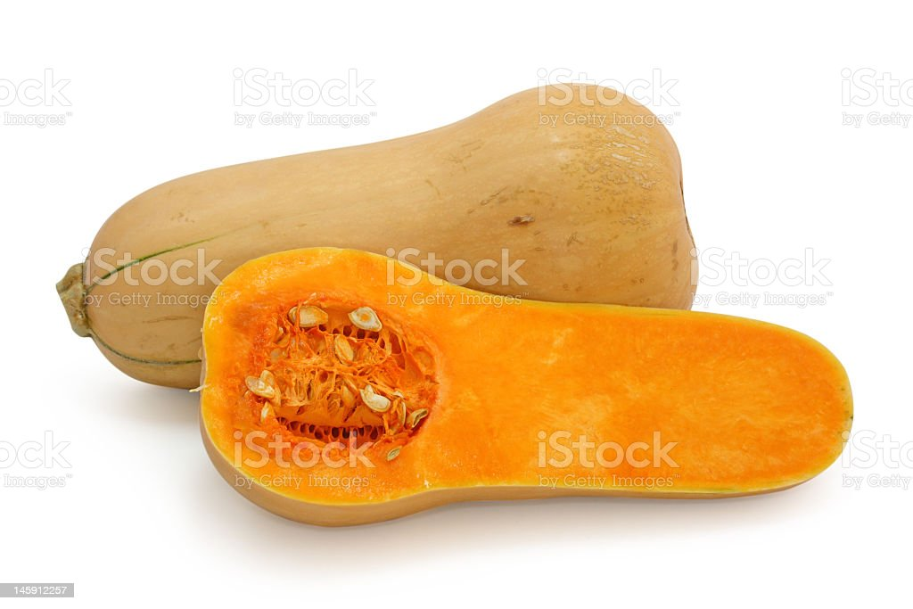 Butternut squash cut in half on white surface stock photo