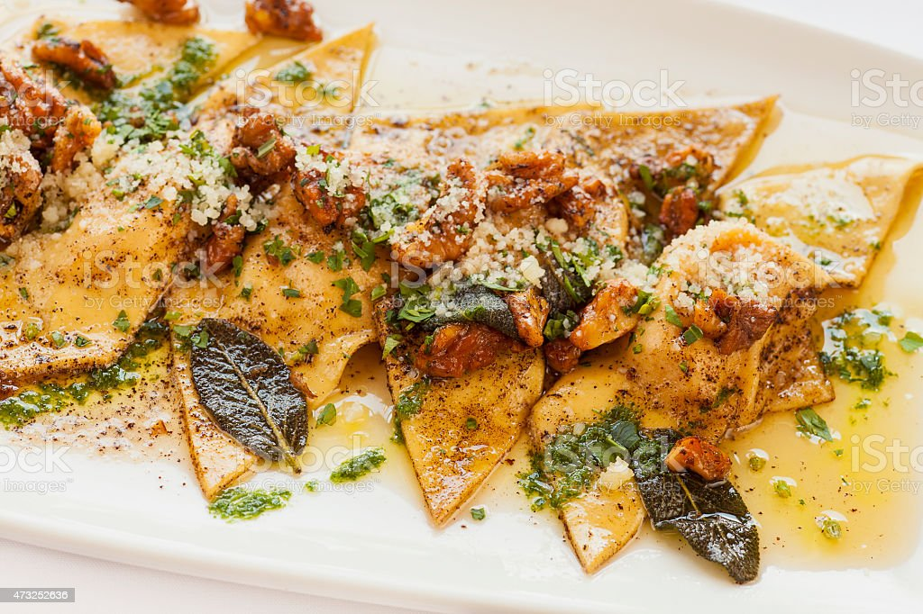 butternut squash ravioli with roasted walnuts and brown butter stock photo