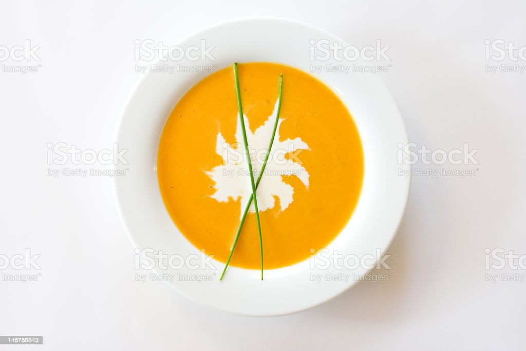 Butternut squash soup with spot of cream and chives stock photo