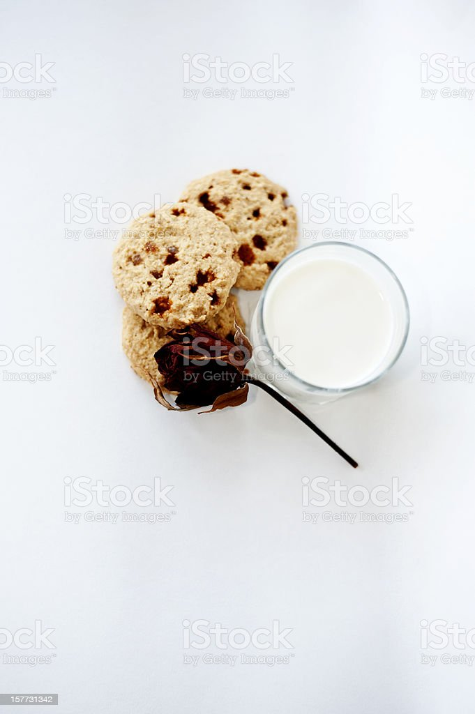 Butterscotch pecan cookies with faded rose and glass of milk royalty-free stock photo