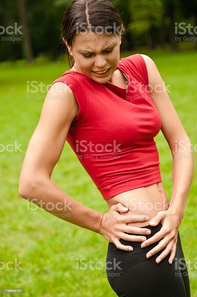Buttocks injury - sportswoman in pain royalty-free stock photo