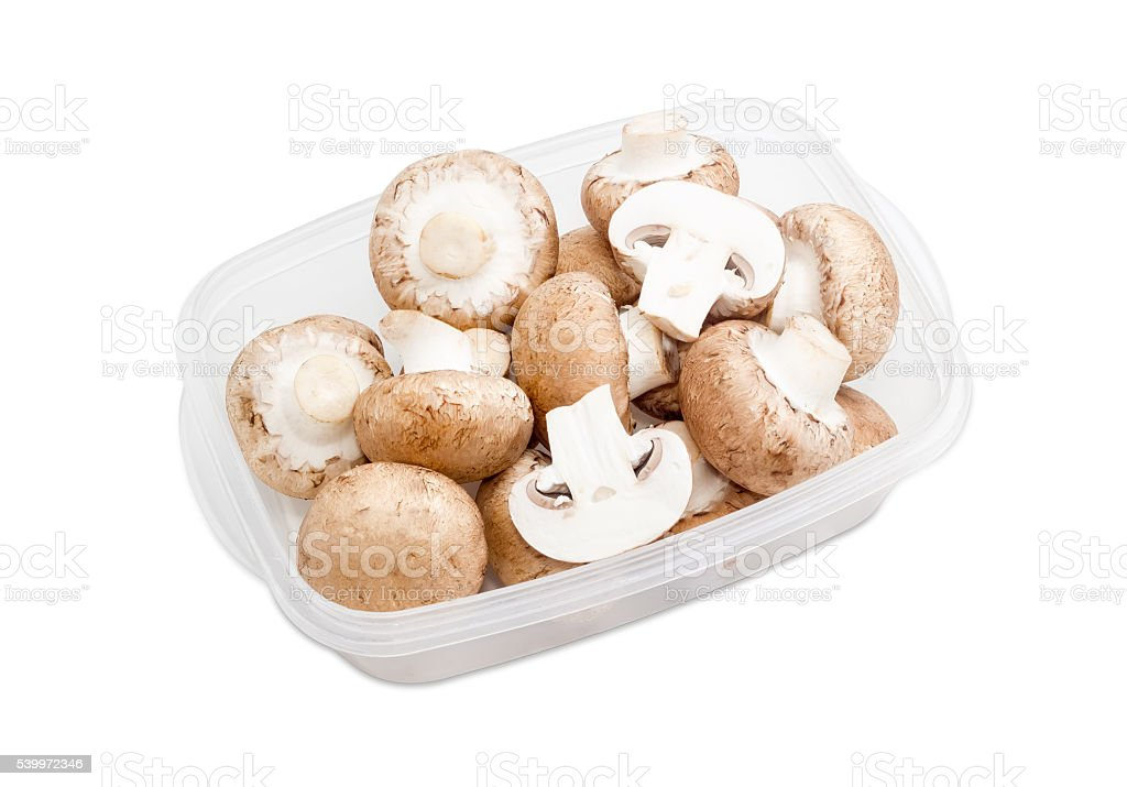 Button mushrooms in a plastic tray on a light background stock photo