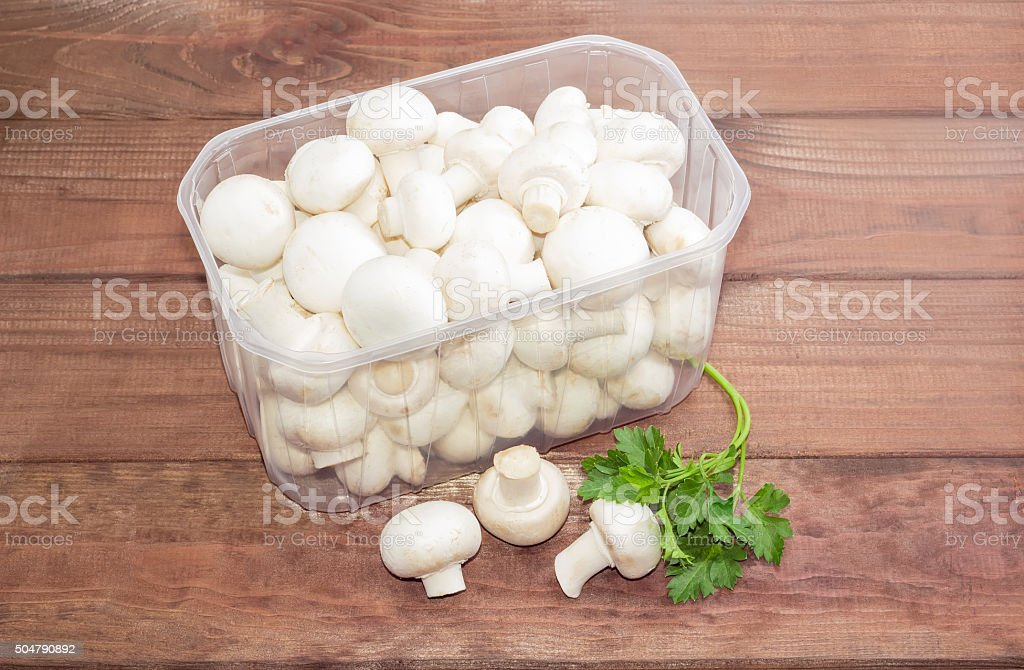 Button mushrooms in a plastic tray on a wooden surface stock photo